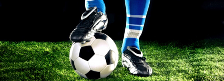 Footballer with his foot on top of a football