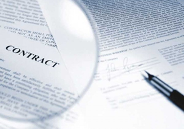 Contract under a magnifying glass with a pen