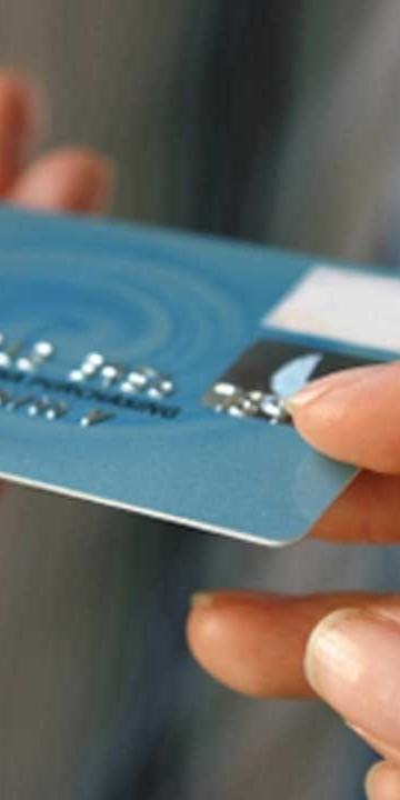 person passing over a credit card