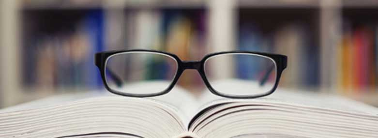 Eyeglasses on top of an open book