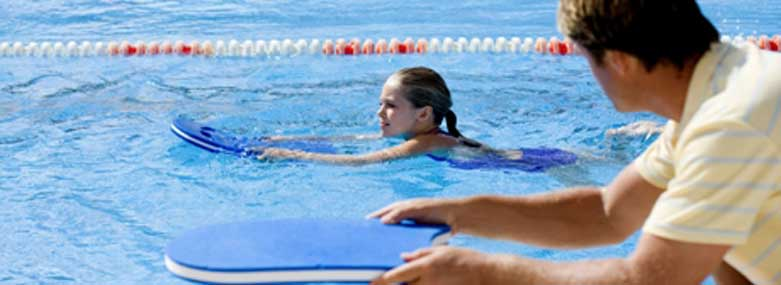 girl learning to swim in a swimming pool with a coach stood on the side of a pool