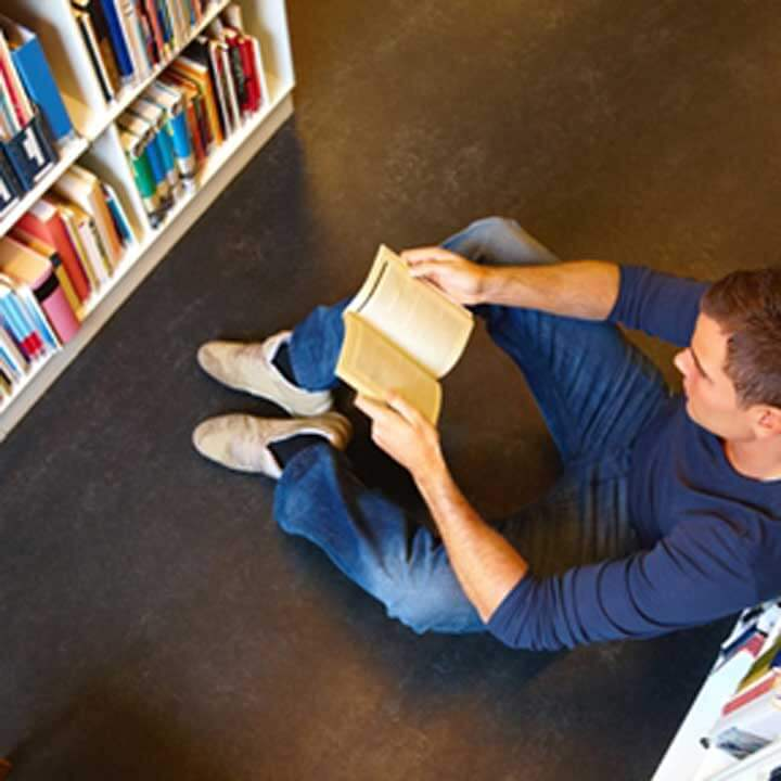 Man sitting on the floor of a library reading a book