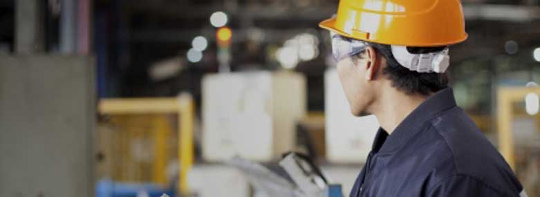 Man in a factory with an orange hardhat on