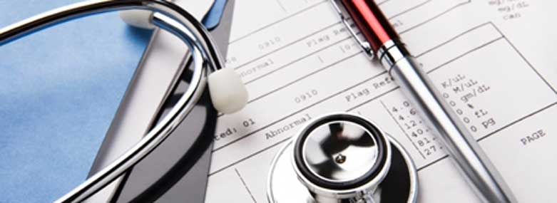 Stethoscope and pen on top of a medical report
