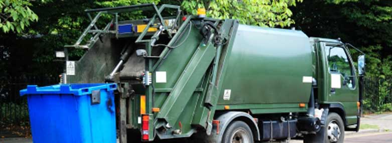 Green waste services truck with blue bins