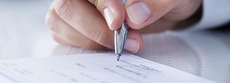 close-up of someone signing a piece of paper