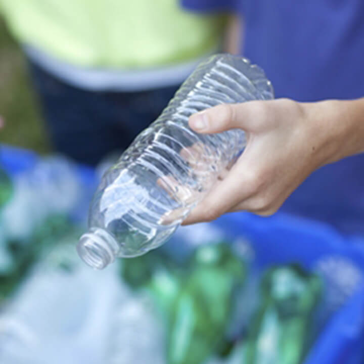 People holding plastic and glass bottles
