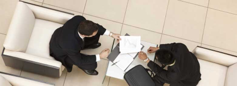 Two men sat down looking at documents