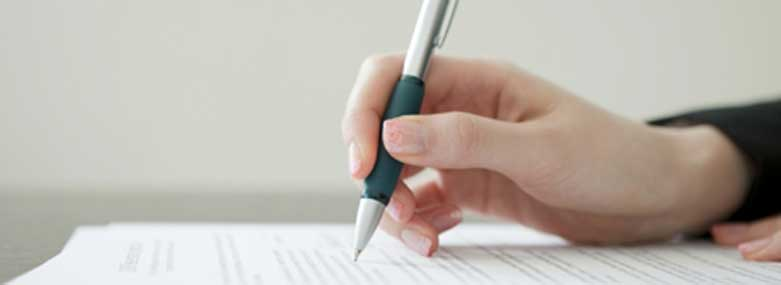 person writing on a document with a silvergreen pen