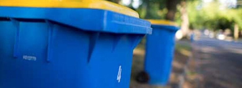 blue plastic wheelie bin with a yellow lid