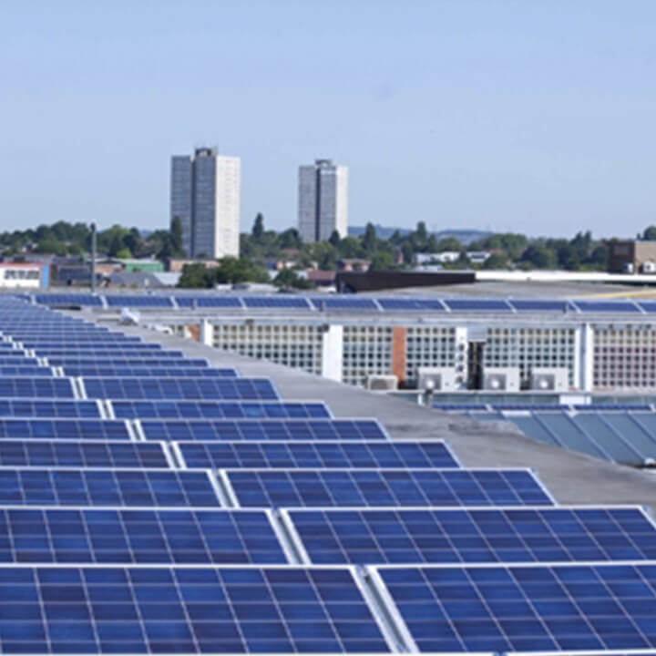 solar panels on the roof of a building with two residential tower blocks in the background