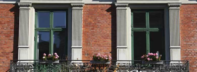 image of two square windows with a balcony and three flowers baskets with pink roses