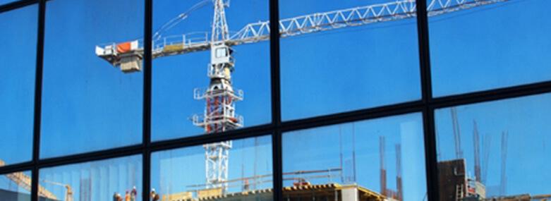A crane on a construction site seen through a window