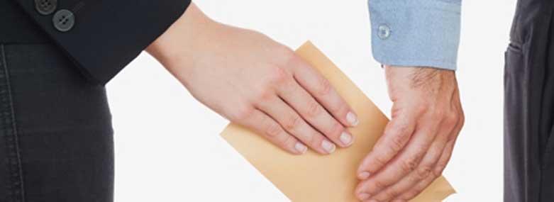 people passing a brown paper envelop between them