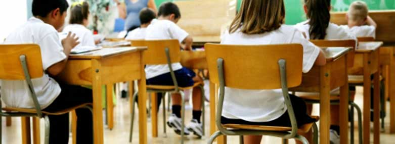 school children sitting at school desks