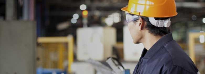Man in a warehouse wearing a hard hat