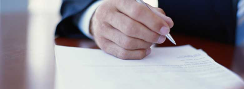 person signing a peice of paper