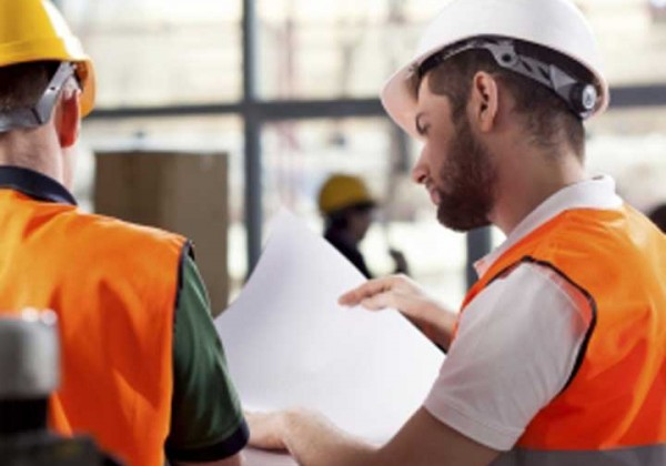 Two men in hard hats and high vis safety vests discussing plans