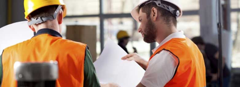 Two men in hi-vis jacket and hard hats looking at a piece of paper