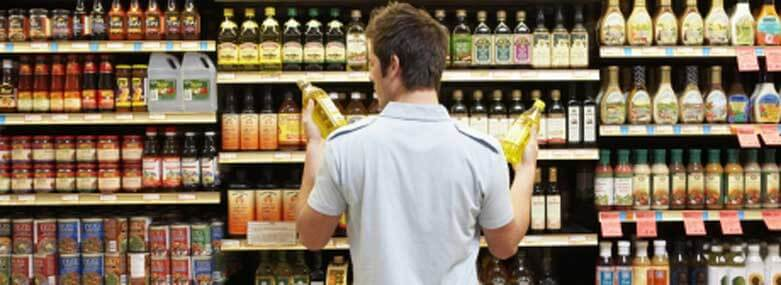 person looking at two bottles of olive oil