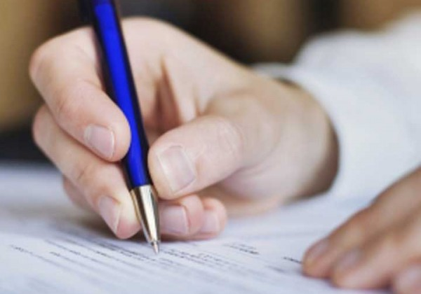 Close up of a man writing on paper with a blue pen