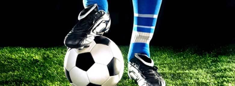 Footballer with a football under his fottball boot