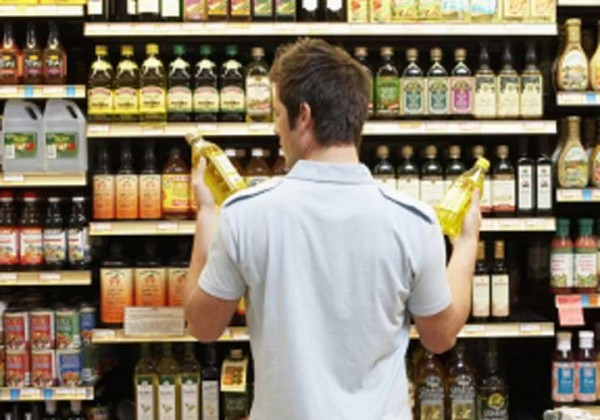 Man looking at two bottles of olive oil food labelling