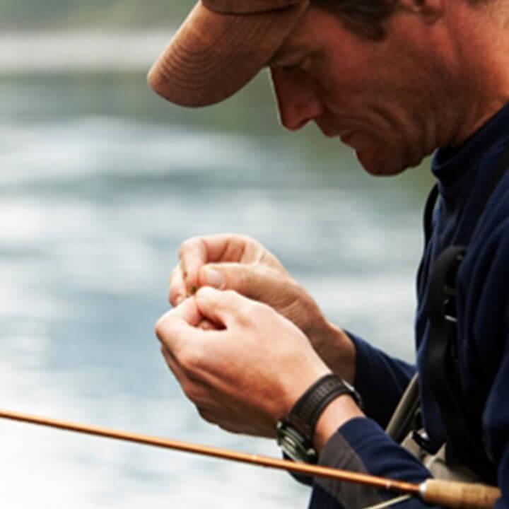 Man attaching bait to rod