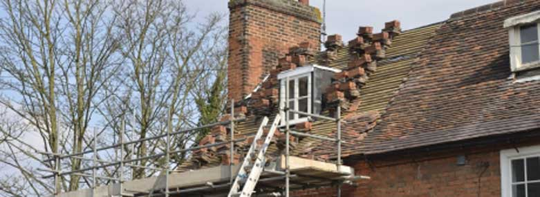 Roof repairs - stripped roof with red tiling, scaffolding anf a ladder