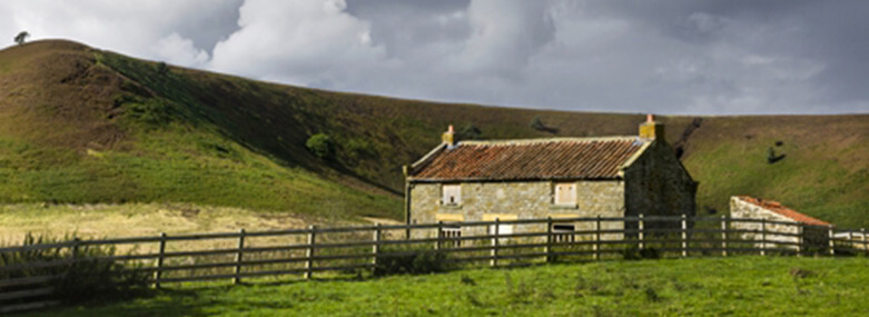 Farmhouse on a hillside with a wooden fence in front