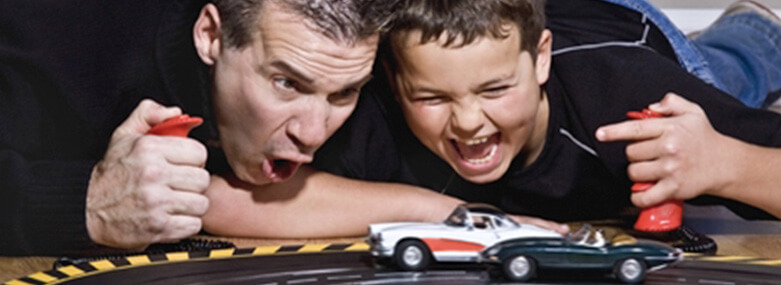 Man and son playing with car track
