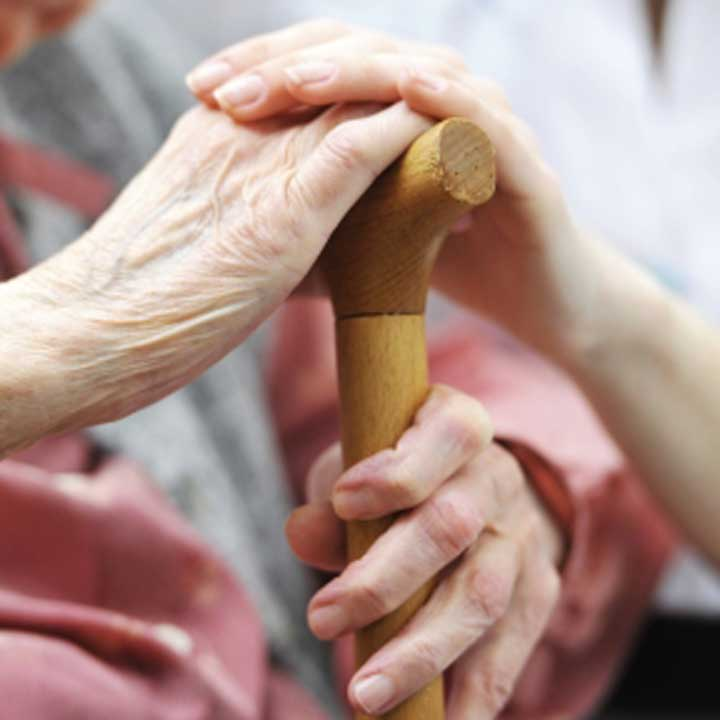 Person holding and elderly persons hand rested ona walking stick