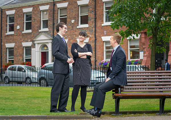 3 people talking, two standing one perched on a park bench arm