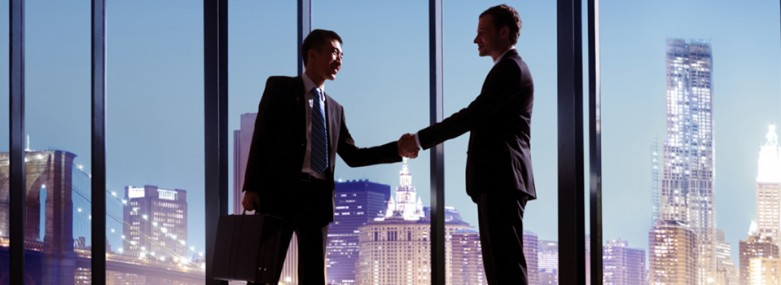 Two businessmen shaking hands in an office shaking hands with a cityscape in the background