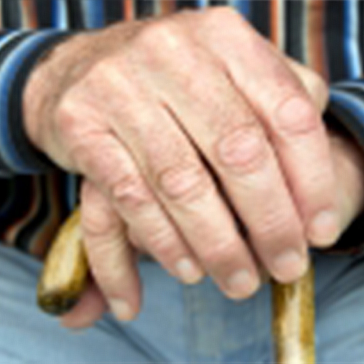old man's hands holding a walking stick