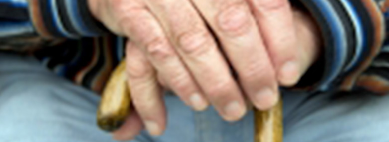 old persons hands on top of a wooden walking stick