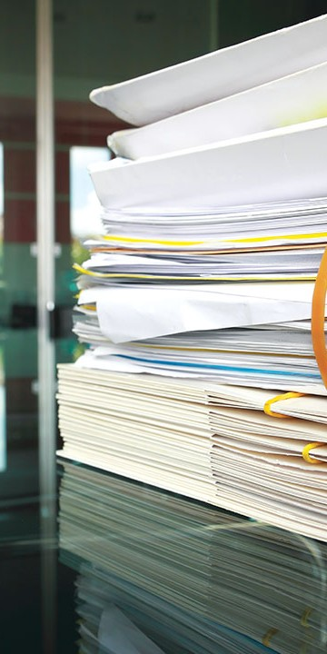 Pile of papers and folders on a meeting room table