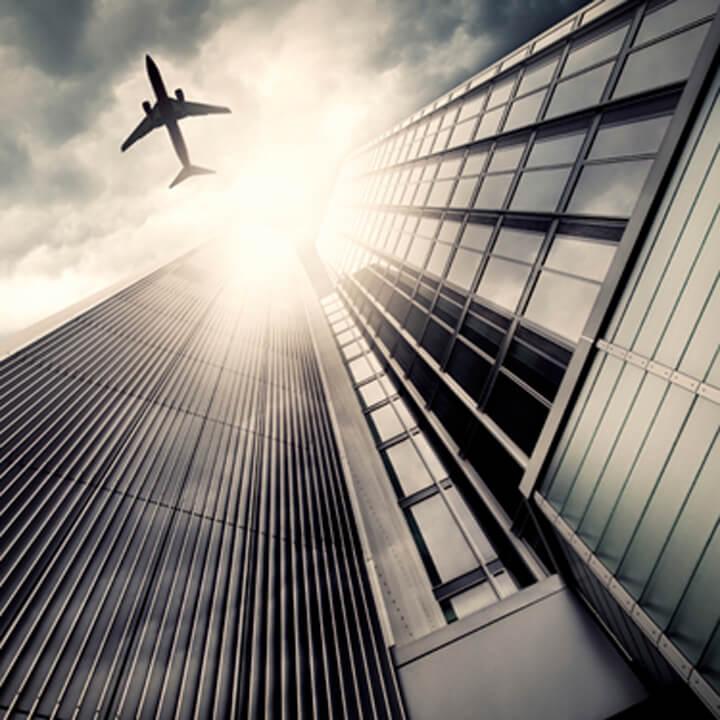 Jet plane flying over skyscraper