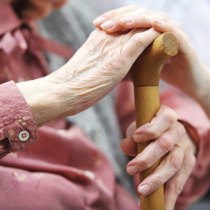 Elderly lady holding a wooden walking stick whilst a care home worker has a hand on top of her's