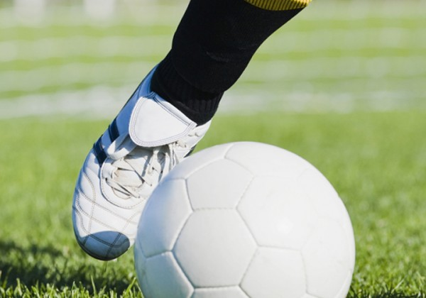 Low section view of a soccer player kicking a soccer ball