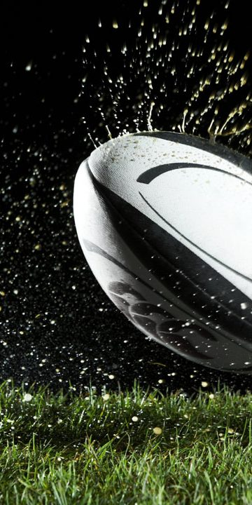 Rugby ball in motion over grass