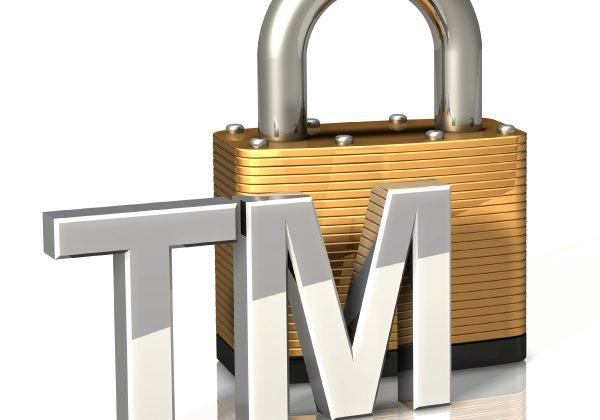 3d illustration of heavy brass padlock on a white surface with a chrome trademark symbol sitting in front of it