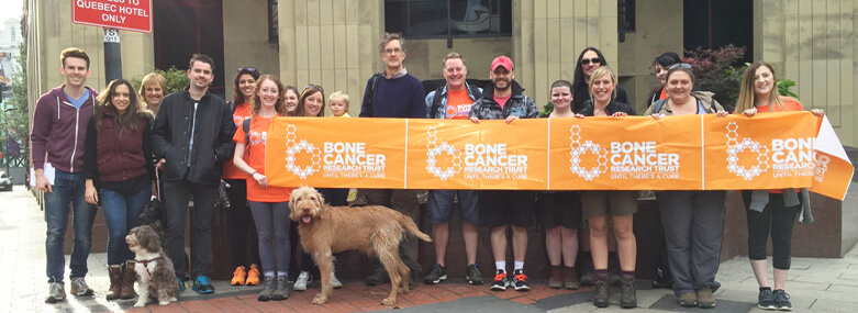 Walkers Walk Fundraising Team outside the offices of Walker Morris LLP with a Bone Cancer Research Trust banner