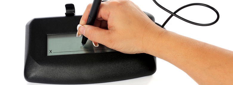 A woman's hand signing an electronic signature pad.
