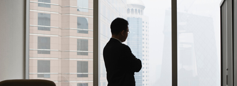 silhouette of a man looking out of a skyscraper window