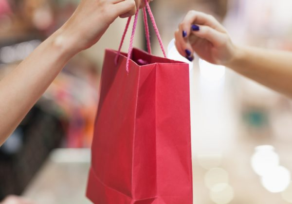 Woman handing over a red shopping bag
