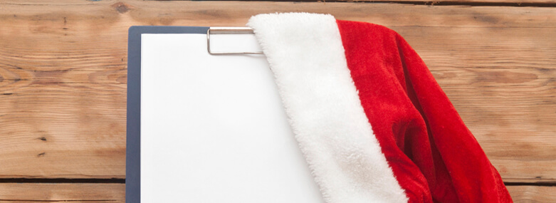 Santa hat on clipboard with blank paper sheet for your text