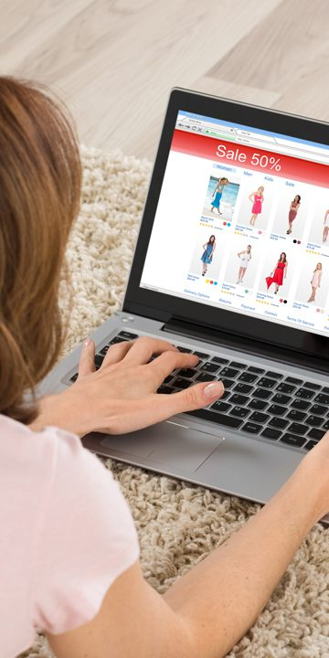 Woman Lying On Carpet Shopping Online On Laptop With Debit Card