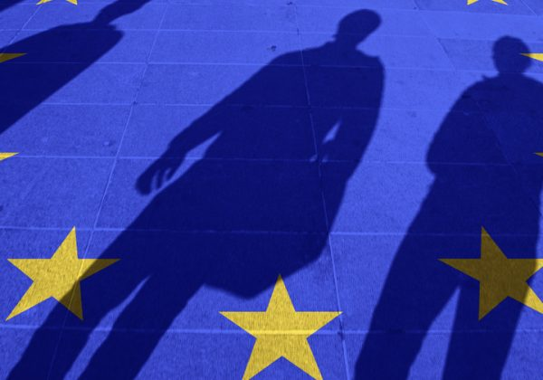 European Union flag painted on tiled street floor and shadows group of people walking at sunny day.