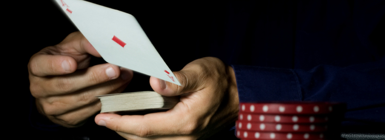 Card player turning over the Ace of Diamonds and a stack of gambling chips next to the player